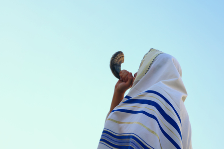 Jewish man blowing the Shofar (horn) of Rosh Hashanah (New Year). Religious symbol.
