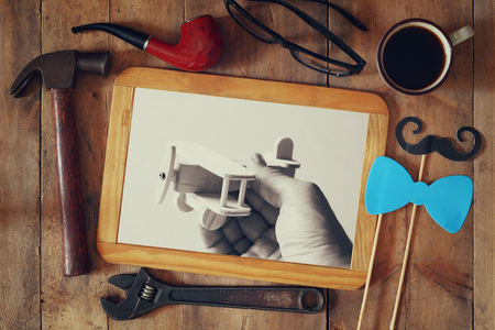 top view image with vintage fathers accessories next to photoframe with old photography Stock Photo