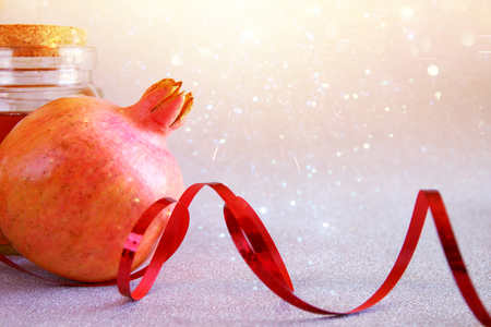 Rosh hashanah (jewesh New Year holiday) concept - pomegranate and honey over glitter background. Traditional symbol
