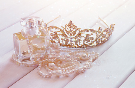 neckless: White pearls necklace, diamond tiara and perfume bottle on toilette table. Selective focus