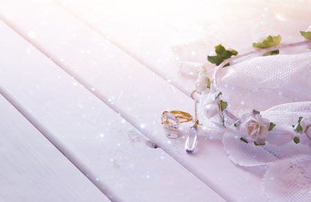 toilette: Dreamy photo of Gold ring and necklace and white floral tiara on toilette table. Selective focus. Glitter overlay Stock Photo