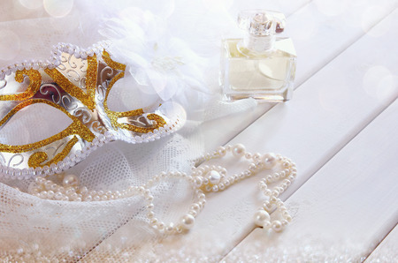 neckless: Dreamy photo of Vintage white venetian mask and pearls on table. Selective focus. Glitter overlay Stock Photo