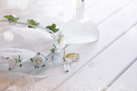 neckless: Dreamy photo of Gold ring and necklace, white floral tiara and perfume bottle on toilette table. Selective focus. Glitter overlay
