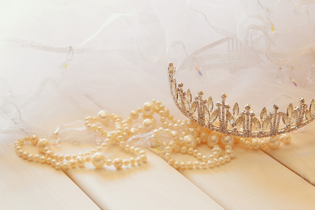diamond necklace: White pearls necklace and diamond tiara on white toilette table. Selective focus Stock Photo