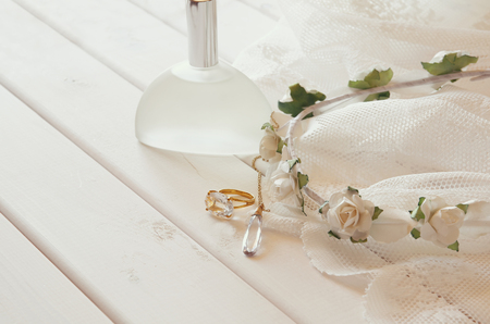 toilette: Gold ring and necklace, white floral tiara and perfume bottle on toilette table. Selective focus