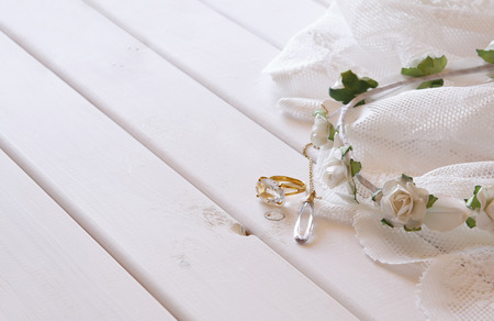 toilette: Gold ring and necklace and white floral tiara on toilette table. Selective focus Stock Photo