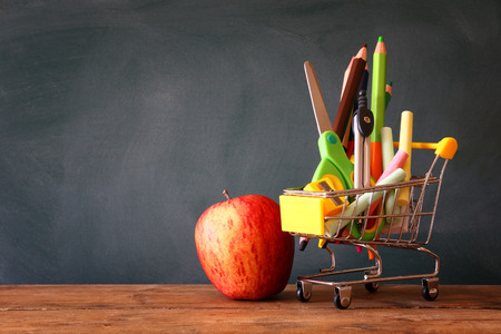 teaching crayons: Shopping cart with school supply and apple in front of blackboard. Back to school concept