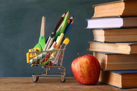 teaching crayons: Shopping cart with school supply, apple and books in front of blackboard. Back to school concept