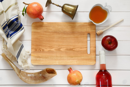 Rosh hashanah (jewish New Year holiday) concept - honey, apple and pomegranate over wooden table. Traditional symbols