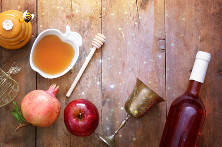 Rosh hashanah (jewish New Year holiday) concept - honey, apple and pomegranate over wooden table. Traditional symbols. Glitter overlay Stock Photo