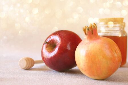 apple and honey: Rosh hashanah (jewesh New Year holiday) concept - pomegranate, honey and apple over glitter background. Traditional symbols