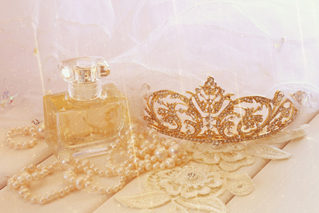 toilette: Dreamy photo of white pearls necklace, diamond tiara and perfume bottle on toilette table. Selective focus. Glitter overlay