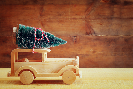 wooden toy: Wooden car carrying a christmas tree. Stock Photo