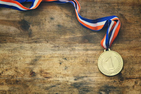 top view image of gold medal over wooden table.