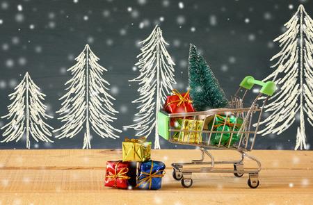Carro de compras con el árbol de navidad y regalos en la mesa de madera. Foto de archivo