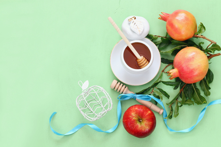 honey apple: Rosh hashanah (jewish New Year holiday) concept - honey, apple and pomegranate over wooden table. Traditional symbols