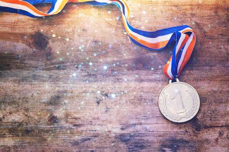 bovenaanzicht beeld van gouden medaille op een houten tafel.