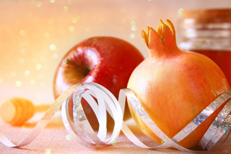 religion ritual: Rosh hashanah (jewish New Year holiday) concept - honey, apple and pomegranate over wooden table. Traditional symbols. Glitter overlay Stock Photo
