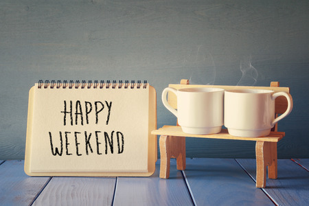 weekend: Couple coffee cups next to notebook with phrase happy weekend on wooden table. vintage filtered