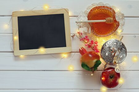 pomegranat: Rosh hashanah (jewesh New Year holiday) concept - apple, pomegranat, honey and blank blackboard for copy space over wooden table. Traditional symbols Stock Photo