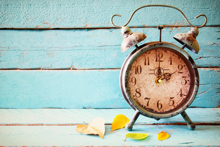 Image of autumn Time Change. Fall back concept. Dry leaves and vintage alarm Clock on a blue rustic wooden background