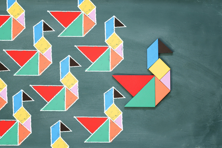 business puzzle: Leadership and creativity concept with tangram puzzle bird leading over chalkboard background