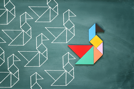 Leadership and creativity concept with tangram puzzle bird leading over chalkboard background