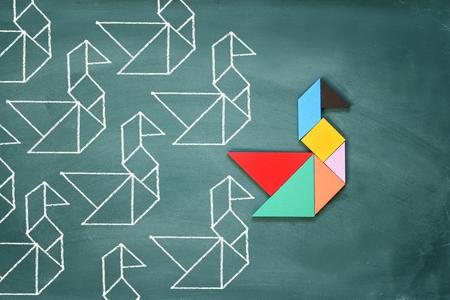 Leiderschap en creativiteit concept met tangram puzzel vogel leidt over bordachtergrond