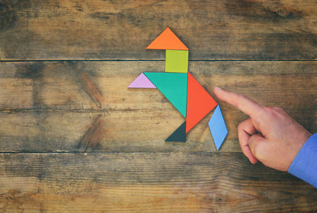 square image: mans hand pointing at horse made from square tangram puzzle, wooden background. retro style image Stock Photo