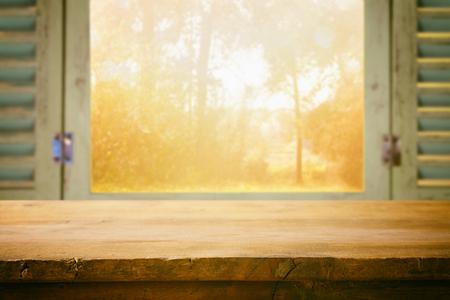 窓からぼやけて秋自然の前で空のテーブルです。製品表示モンタージュの準備ができて
