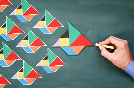 Leadership creativity Concept. image of male hand drawing boats over chalkboard. the heading boat is made of tangram puzzle shape. filtered photo Stock Photo