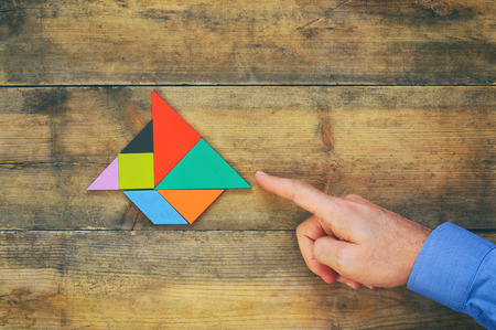 square image: mans hand pointing at boat made from square tangram puzzle, wooden background. retro style image Stock Photo