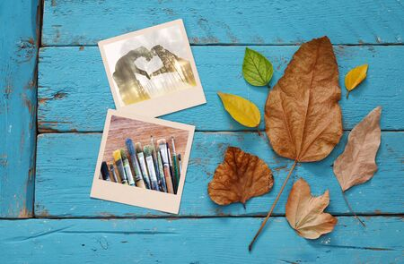 hojas antiguas: Autumn background with dry leaves and old photo frames on blue wooden table Foto de archivo