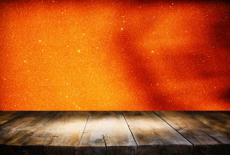 holiday lights display: Halloween holiday concept. Empty rustic table in front of orange glitter lights background. Ready for product display montage Stock Photo