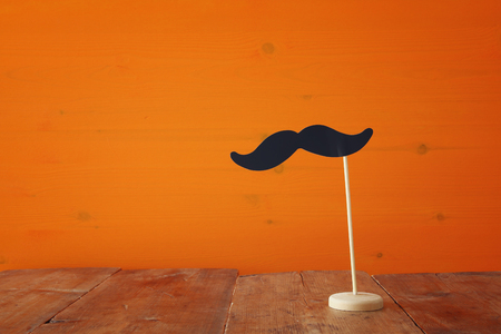 halloween concept: Halloween holiday concept. Funny paper moustache, on wooden table Stock Photo