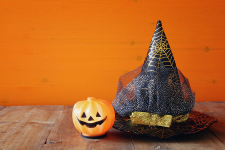 Halloween holiday concept. Witch hat next to cute pumpkin on wooden table Stock Photo