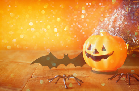 Halloween holiday concept. Cute pumpkins on wooden table. Glitter lights overlay