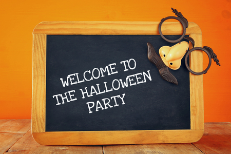Halloween holiday concept. Blackboard with funny mask, on wooden table Stock Photo