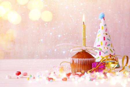 tortas de cumpleaños: concepto de cumpleaños con la magdalena y de la vela, sombrero del partido en la mesa de madera. Brillo ilumina superposición