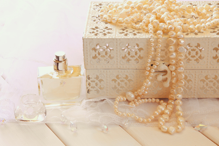 neckless: White pearls necklace and perfume bottle on toilette table. Selective focus. Vintage filtered