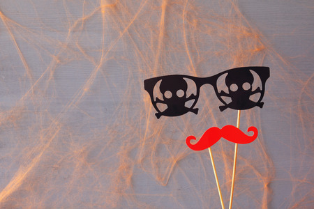 funny glasses: Halloween holiday concept. Funny paper moustache and pirate glasses