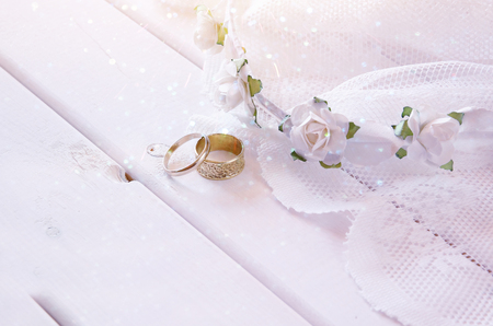 toilette: Dreamy photo of Wedding rings and white floral tiara on toilette table. Selective focus. Glitter overlay