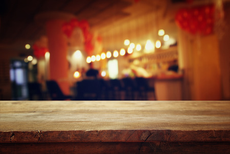 bar top: Image of wooden table in front of abstract blurred background of restaurant lights