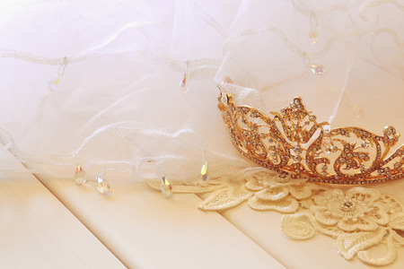 Vintage tulle chiffon bride dress and gold diamond tiara on wooden table. Wedding concept. Selective focus