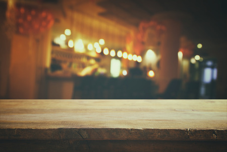 Image of wooden table in front of abstract blurred background of restaurant lights. Retro filtered