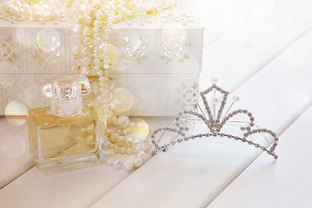 toilette: Dreamy photo of white pearls necklace, diamond tiara and perfume bottle on toilette table. Selective focus. Vintage filtered Stock Photo