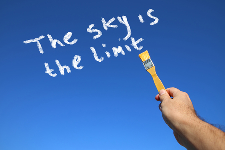 sky is the limit: man hand holading paint brash in front of clear blue sky with the text the sky is the limit