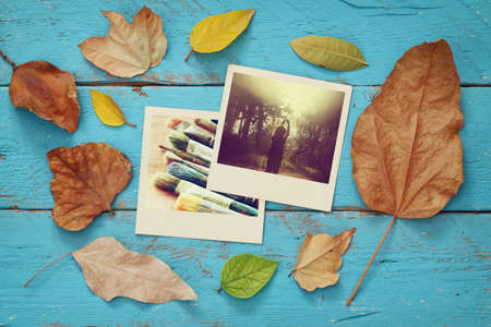 table scraps: Autumn background with dry leaves and old photo frames on blue wooden table Stock Photo
