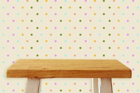portada: pequeña mesa vacía delante de fondo retro. Para la exhibición de productos. Foto de archivo