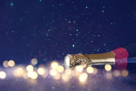 Immagine astratta di bottiglia di champagne e luci festive. Nuovo anno e celebrazione concetto